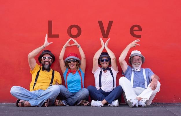 Twee stellen senior en middelbare leeftijd die het woord liefde met handen proberen te schrijven