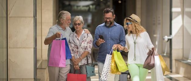 Twee stellen van twee volwassenen en twee senioren gaan samen winkelen in het winkelcentrum met veel tassen met kleding en meer aan hun handen - vier personen - man met telefoon