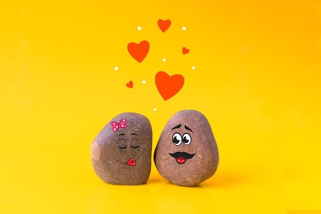 Twee stenen met getekende grappige gezichten verliefd op elkaar op gele achtergrond. liefde, valentijnsdag concept.
