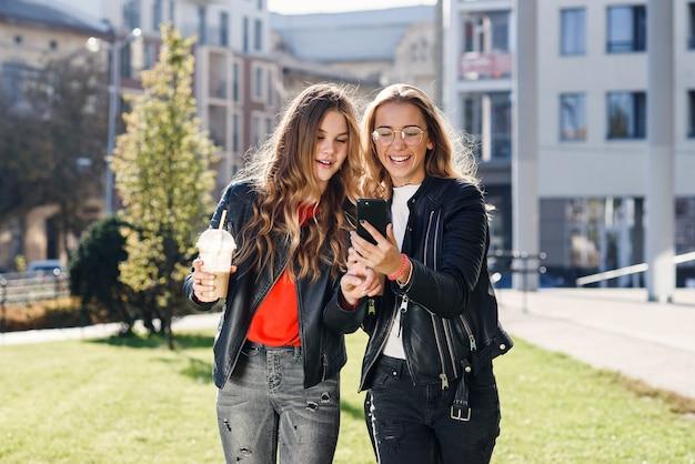 Twee stijlvolle aantrekkelijke tienermeisjes met smoothie en smartphone in de buurt van winkelcentrum in het stadscentrum.