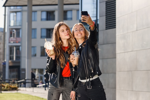 Twee stijlvolle aantrekkelijke tienermeisjes met smoothie en smartphone in de buurt van winkelcentrum. vrije tijd met beste vrienden.