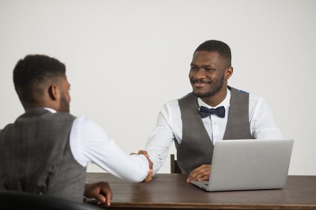 Twee stijlvolle afrikaanse mannen in pak zitten aan de tafel met een laptop op een witte muur