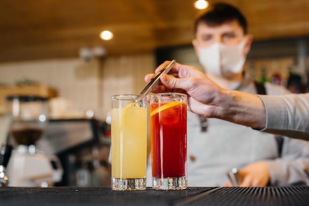 Twee stijlvolle barmannen in maskers en uniformen tijdens de pandemie, cocktails bereiden. het werk van restaurants en cafés tijdens de pandemie.
