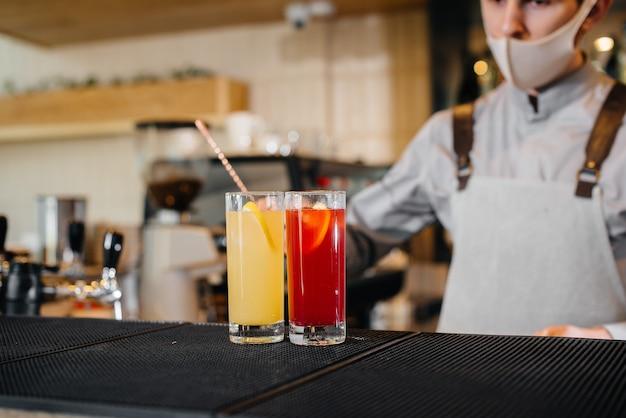 Twee stijlvolle barmannen in maskers en uniformen tijdens de pandemie, cocktails bereiden