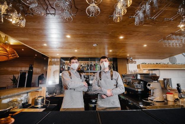 Twee stijlvolle barmannen in maskers en uniformen tijdens de pandemie, staan achter de bar