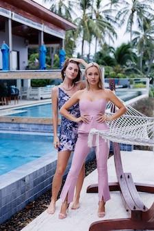 Twee stijlvolle blanke vrouw in zomerjurk en roze trendy pak
