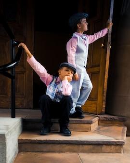 Twee stijlvolle broertjes in formele kleding bij de trap voor een deur