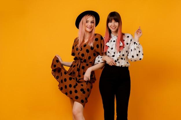 Twee stijlvolle elegante vrouwen in jurken poseren over gele muur