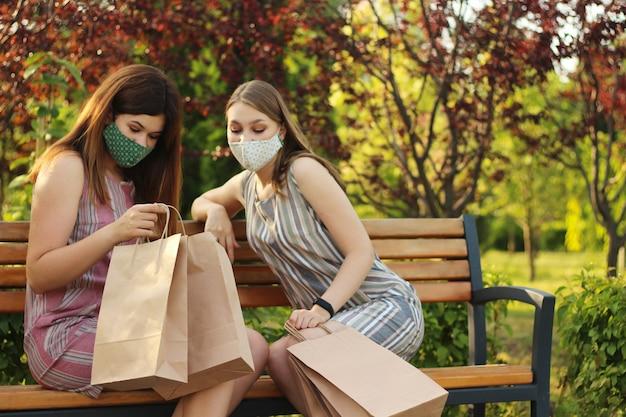 Twee stijlvolle en aantrekkelijke meisjes in beschermende maskers met tassen na het winkelen zitten in het park