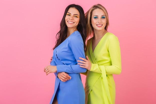 Twee stijlvolle glimlachende aantrekkelijke vrouwen dragen kleurrijke jurken met plezier poseren op roze muur, blauwe en gele kleur kleding, zomer modetrend