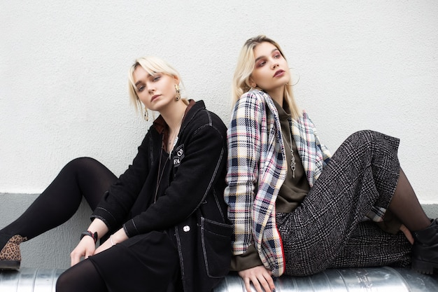 Twee stijlvolle jonge blonde vriendinnen in oversized stijlvolle jassen in modieuze leren laarzen zitten op een vintage zilveren pijp in de buurt van de muur op straat