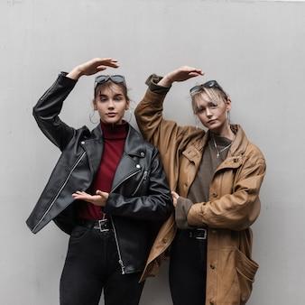 Twee stijlvolle jonge vrouwenmodellen in een modieus leren jack met een trui en spijkerbroek poseren in de buurt van een grijze muur in de stad