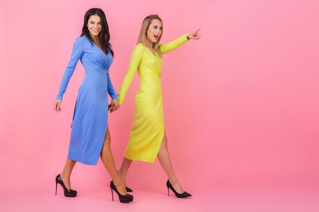 Twee stijlvolle lachende aantrekkelijke vrouwen lopen samen volledige hoogte op roze muur in stijlvolle kleurrijke jurken van blauwe en gele kleur, lente modetrend, wijzende vinger