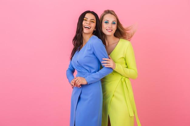 Twee stijlvolle lachende aantrekkelijke vrouwen plezier poseren op roze muur in stijlvolle kleurrijke jurken van blauwe en gele kleur, lente modetrend