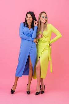 Twee stijlvolle lachende aantrekkelijke vrouwen poseren volledige hoogte op roze muur in stijlvolle kleurrijke jurken van blauwe en gele kleur, lente modetrend