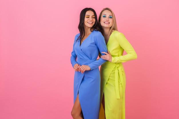 Twee stijlvolle lachende aantrekkelijke vrouwen vrienden poseren op roze muur in stijlvolle kleurrijke jurken van blauwe en gele kleur, lente modetrend