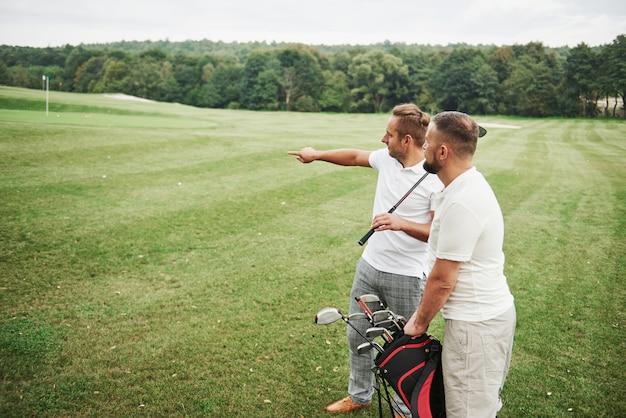 Twee stijlvolle mannen die tassen met clubs houden en op golfbaan lopen
