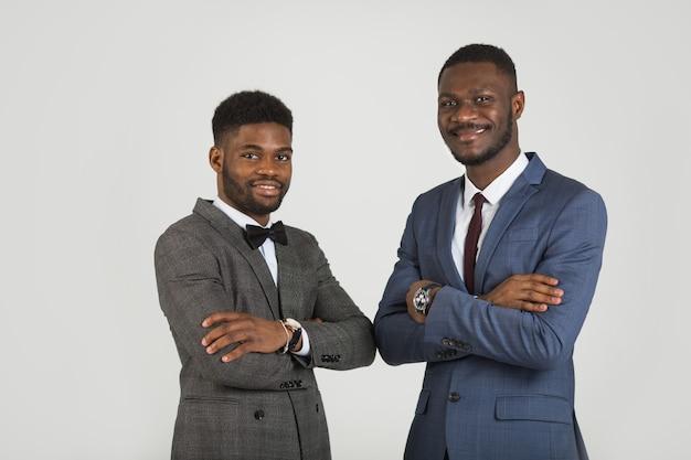 Twee stijlvolle mannen in pak op een grijze achtergrond
