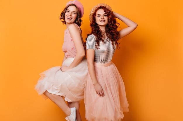 Twee stijlvolle meisjes dansen met een glimlach. studio shot van schattige modieuze dames geïsoleerd op gele achtergrond.