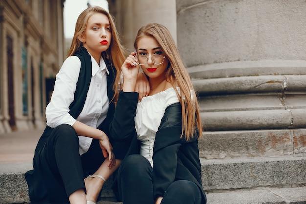 Twee stijlvolle meisjes in een zomerstad