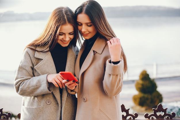 Twee stijlvolle meisjes rusten uit in een stad