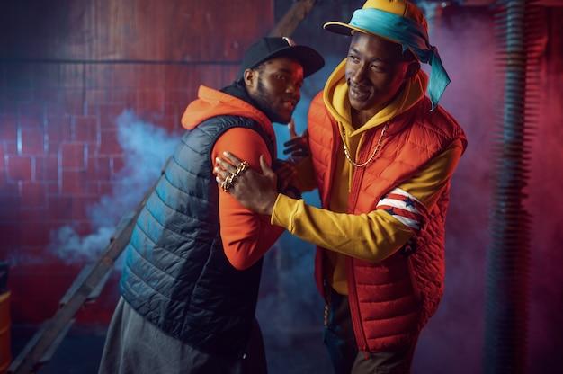 Twee stijlvolle rappers met gouden sieraden in coole studio, ondergrondse decoratie