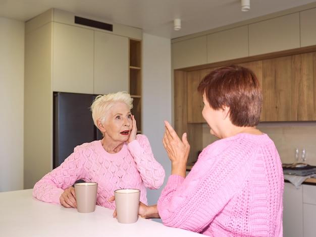 Twee stijlvolle senior vrouwen in roze truien zitten met mokken bij moderne keuken roddelen