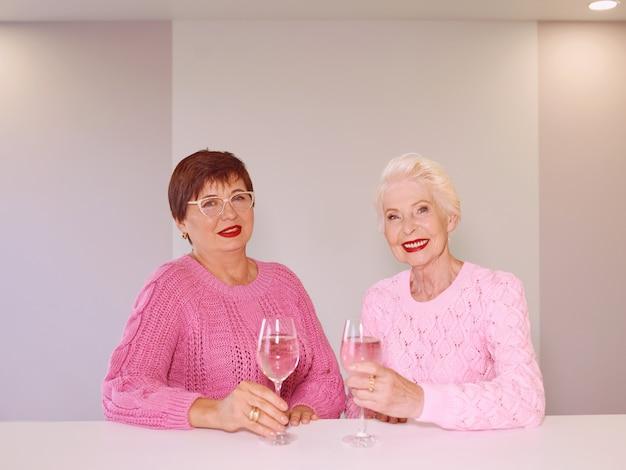 Twee stijlvolle senior vrouwen in roze truien zitten met wijnglazen in bar praten