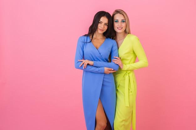 Twee stijlvolle sexy aantrekkelijke vrouwen poseren op roze muur in stijlvolle kleurrijke jurken van blauwe en gele kleur, zomer modetrend