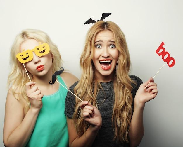 Twee stijlvolle sexy hipster meisjes beste vrienden klaar voor feest, over grijze achtergrond