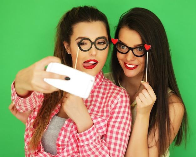 Twee stijlvolle sexy hipster meisjes beste vrienden klaar voor feest, over groene achtergrond