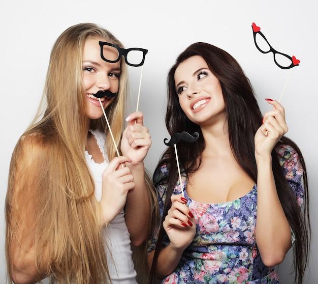 Twee stijlvolle, sexy hipstermeisjes, beste vrienden klaar voor een feestje