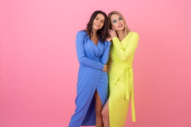 Twee stijlvolle sexy lachende aantrekkelijke vrouwen poseren op roze muur in stijlvolle kleurrijke jurken van blauwe en gele kleur, zomer modetrend