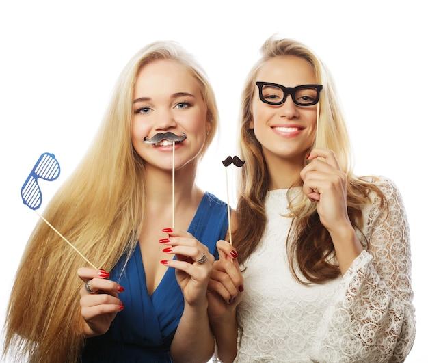 Twee stijlvolle sexy meisjes beste vrienden klaar voor feest, op witte achtergrond