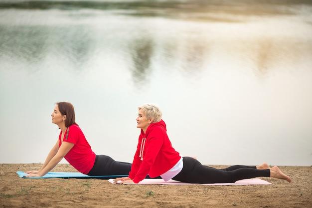 Twee stijlvolle volwassen vrouwen doen in de zomer buitensporten