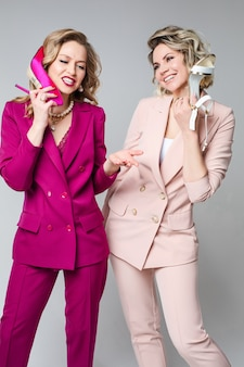 Twee stijlvolle, vrolijke zakenvrouwen die pakken dragen, tonen een telefoon die schoenen aandoet. advertentiefoto van kledingverkoop en winkelen. hoge kwaliteit foto