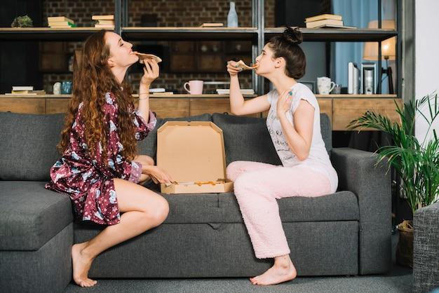 Twee stijlvolle vrouwelijke vrienden die pizza eten