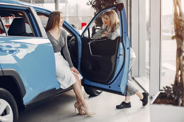 Twee stijlvolle vrouwen in een autosalon