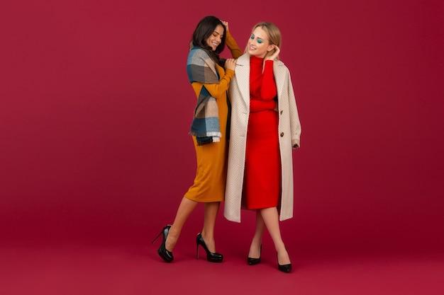 Twee stijlvolle vrouwen in herfst winter mode jurk en jas poseren geïsoleerd op rode muur