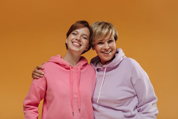 Twee stijlvolle vrouwen met kort modern kapsel en modieuze roze hoodies glimlachend en knuffelen op geïsoleerde oranje achtergrond.