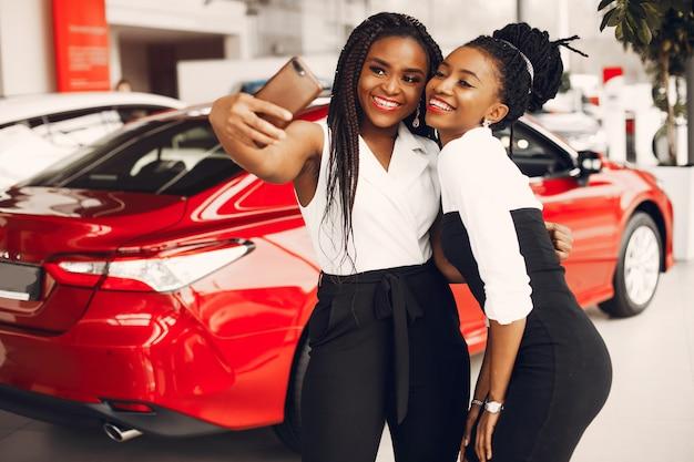 Twee stijlvolle zwarte vrouwen in een autosalon