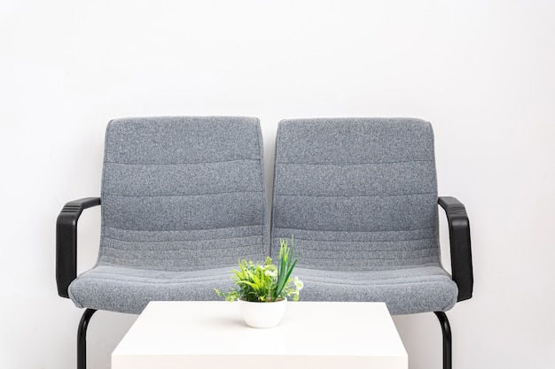Twee stoelen in een wachtkamer met witte tafel en witte achtergrond, witte achtergrond en kopieerruimte