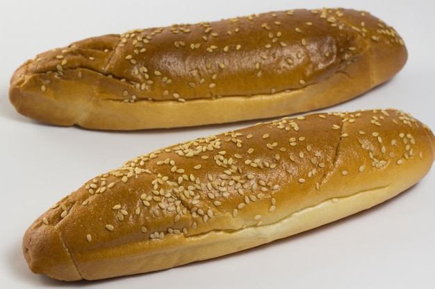 Twee stokbrood besprenkeld met sesamzaadjes op een witte achtergrond