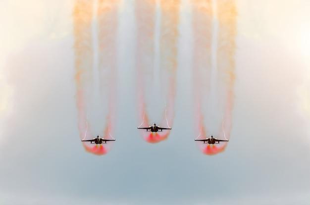 Twee straaljagers vliegen samen met rode rook.