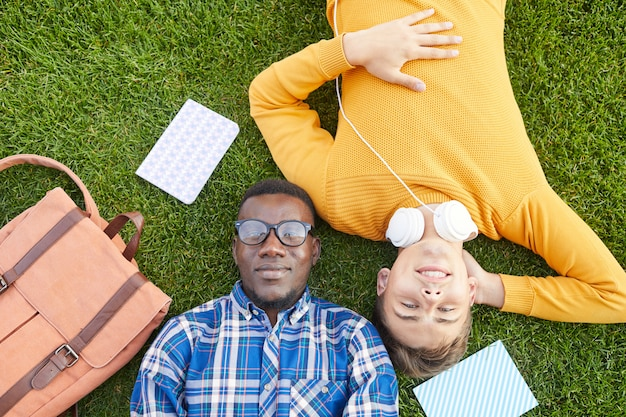 Twee studenten die op gras leggen