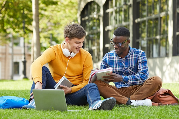 Twee studenten die op gras zitten
