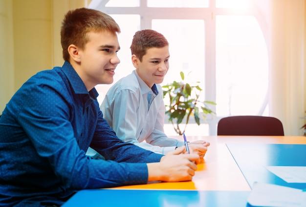 Twee studenten in de klas. jongens die vrolijk aan tafel zitten te glimlachen. educatief concept.