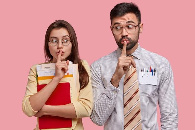 Twee studenten maken stilte-teken, vragen om hun geheim niet te vertellen, bereiden iets grandioos voor, dragen de nodige papieren, gekleed in formele kleding