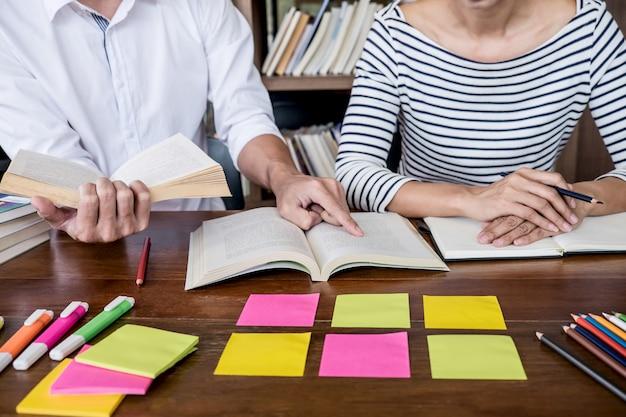 Twee studenten of klasgenoten groep zitten in de bibliotheek met helpt vriend huiswerk en les oefenen
