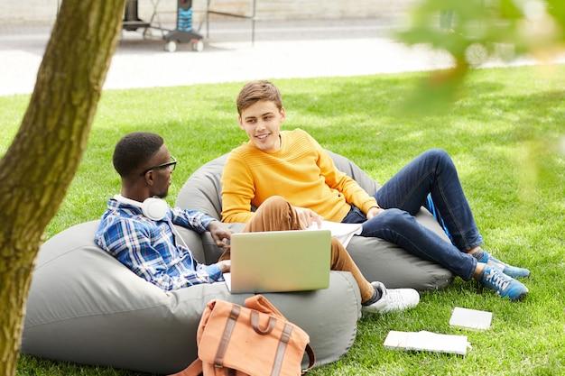 Twee studenten ontspannen buiten op de campus